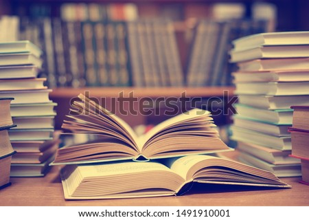 Education learning concept with opening book or textbook in old library, stack piles of literature text academic archive on reading desk and aisle of bookshelves in school study class room background Royalty-Free Stock Photo #1491910001
