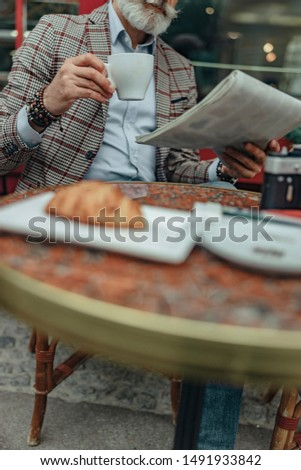 Senior man holding newspaper and cup of hot drink stock photo #1491933842