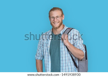 Smiling confident young bearded handsome man student hold backpack look at camera, hipster casual guy university teacher stand with rucksack isolated on blue studio background, portrait, copy space