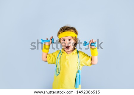 Fitness child. Sporty boy with jump rope and dumbbells. Gym workout. Boy in sportwear with skipping rope and dumbbells. Child sportsman. Childhood activity. Sport. Fitness, health and energy. Success. #1492086515