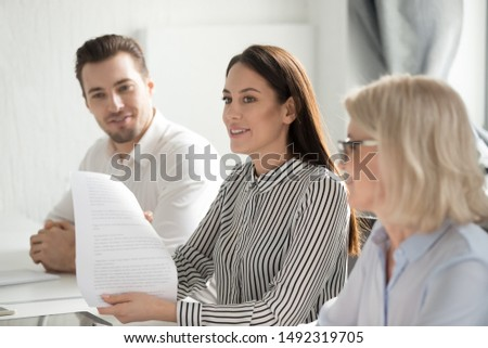 Young businesswoman holding paper document, sharing ideas at business briefing, employees listening to colleague at meeting, partners discussing project, startup ideas during negotiations close up #1492319705