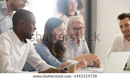 Smiling diverse employees listening to businesswoman coach at briefing, mentor explaining strategy, training staff, using laptop, helping with software, team building activity, horizontal photo #1492319738