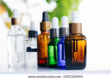 Multi-colored glass dropper bottles over green plants on white background. Vials with pipette plastic caps for essential oils, perfumes and skincare substances. Four in a row, one behind the other. #1492320494