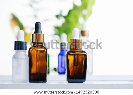 Transparent multi-colored cosmetic glass dropper bottles over green plants on white background. Vials with pipette plastic caps for essential oils, perfumes and skincare substances plased disorderly. #1492320500