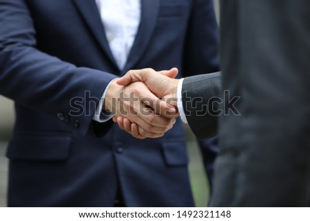 midsection of two business people shaking hands in outdoor #1492321148