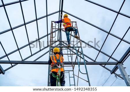Construction worker wearing safety harness using secondary safety device connecting into 15 mm static rope using as fall restraint shingle on top of the new roof. Royalty-Free Stock Photo #1492348355