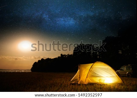 Traveling and camping concept - camp tent at night under a sky full of stars. Orange illuminated tent and car. Beautiful nature - field, forest, plain. Moon and moonlight #1492352597