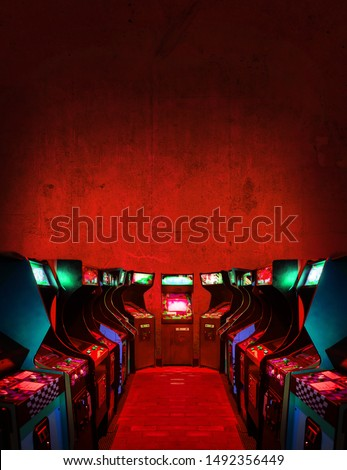 Old Unbranded Vintage Arcade Video Games in a dark gaming room with red light with glowing displays and concrete wall - vertical photo of retro design with free copy space for a poster or magazine