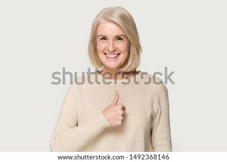 Smiling mature woman in sweater isolated on grey studio background show thumbs up recommend service, happy positive senior lady give sincere recommendation, advice good or sale offer #1492368146