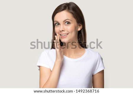 Smiling millennial girl in white t-shirt isolated on grey studio background look at camera tell secret private information, young woman whispering share sale promotion offer or deal, gossip or hearsay #1492368716