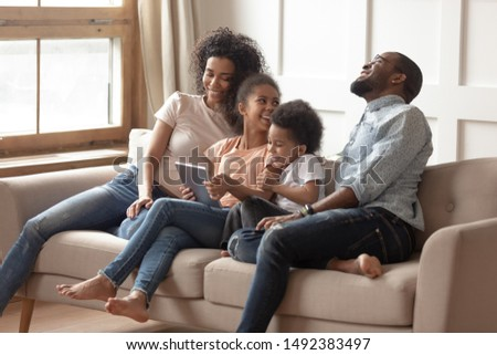 Pre-teen daughter enjoy time with mum dad brother african family sit on couch with tablet having fun using online new apps, internet entertainments, parental control wireless modern tech user concept #1492383497