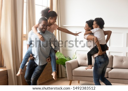 Cheerful mixed-race family playing in living room feels happy move at new house, mother hold piggyback riding son, father carrying daughter people having fun enjoy leisure active game together at home #1492383512