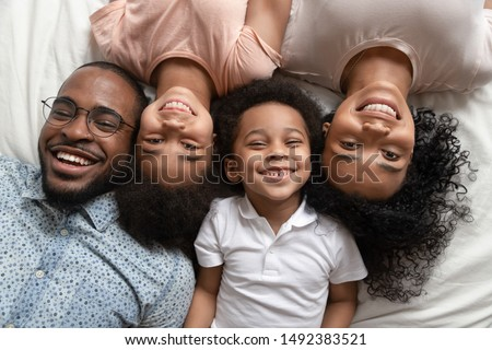 Cheerful african full family married couple with children son and daughter lying down together on bed white bedding smiling looking at camera feels happy. Concept of love, offspring, close up top view #1492383521