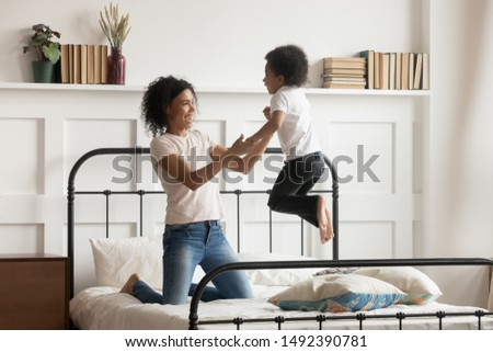 Babysitter mixed-race woman spend day with little boy kid having fun jumping on bed loving mother playing with son holding hands enjoy priceless time with offspring, leisure activities at home concept #1492390781