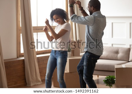 Mixed-race wife and husband millennial couple dancing near big cardboard boxes spouses celebrating moving day at new first own dwelling feels happy, living together cohabitation, life changes concept #1492391162
