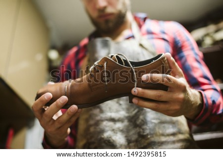 Young shoemaker in the workshop #1492395815