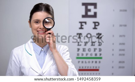 Smiling optometrist looking through magnifying glass and smiling, sight test Royalty-Free Stock Photo #1492458359