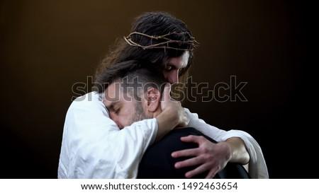 Redeemer hugging unhappy man, faith in God, spiritual protection, eternity