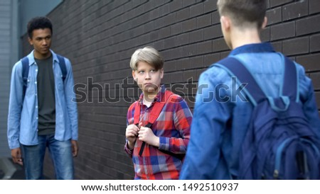 Cruel teenagers threatening younger boy, physical intimidation, school bullying #1492510937