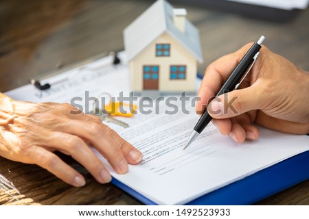 Close-up Of A Real Estate Agent's Hand Helping Client In Filling Contract Form Over Desk #1492523933