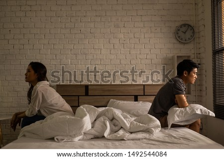 Asian couples quarrel sit in bed ,they argue not to talk to each other. They are unhappy   #1492544084