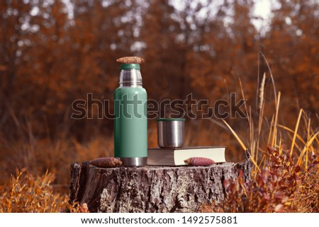 Green thermos, cup and book stand on a stump in the autumn forest. Forest background blurred #1492575881