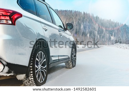 Modern Suv car stay on roadside of winter road. Family trip to ski resort concept. Winter or spring holidays adventure. car on winter snowy road in mountains #1492582601