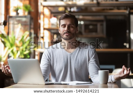 Calm healthy businessman meditate at work desk feeling zen no stress free relief, mindful young man taking break doing yoga exercise relax breath fresh air for peace of mind sit in office cafe Royalty-Free Stock Photo #1492614221