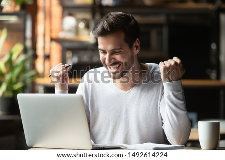 Excited overjoyed young business man student winner looking at laptop celebrate bet bid win online success victory new opportunity sit at cafe table, read good internet email news, got new job offer Royalty-Free Stock Photo #1492614224
