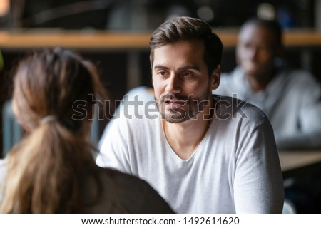 Young serious man having conversation with woman girlfriend sit at cafe table, focused male friend talking to female colleague client solving problem discuss work issues at meeting in coffeehouse #1492614620