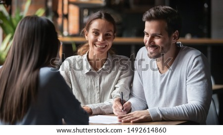 Happy young customers couple ready to sign bank loan agreement meeting broker agent, smiling husband and wife consider finance investing insurance contract deal decide on lease offer listen insurer