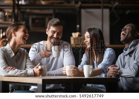 Happy multiracial friends group laugh drink tea in cafe, diverse young students talk enjoy coffee at coffeehouse meeting, multicultural people sit at table having fun together multi-ethnic friendship