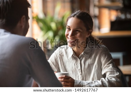 Smiling young woman talking to male friend boyfriend at meeting or romantic date in cafe, happy pretty millennial girl having conversation flirting with man sit at restaurant table drinking coffee #1492617767