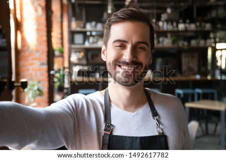 Smiling young male waiter wear apron take selfie looking at camera, head shot portrait of happy businessman entrepreneur small cafe business owner posing making photo recording video, phone cam view