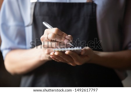 Waitress small cafe business owner wear apron uniform holding notepad pen write notes take order in restaurant, retail serving waiting staff, hospitality, good customer service concept, close up view Royalty-Free Stock Photo #1492617797