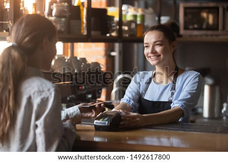 Female customer holding phone near nfc terminal make contactless mobile payment with smiling waitress barista saleswoman on coffeeshop counter, woman client pay in cafe with cellphone via pos machine Royalty-Free Stock Photo #1492617800