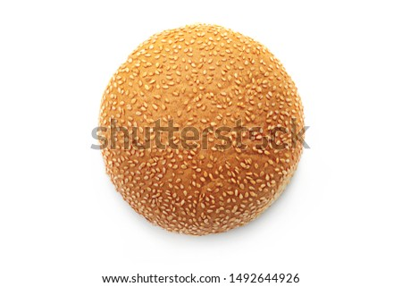 Flat lay round bun with sesame seeds for hamburger isolated on a white background. Top view of a fresh baked ruddy bun #1492644926