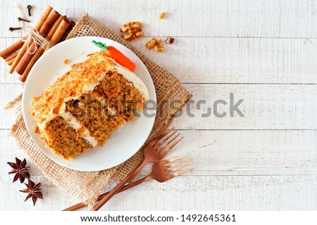 Slice of homemade carrot cake with cream cheese frosting. Above view over a rustic white wood background. #1492645361
