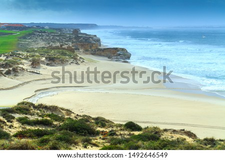 A ocean waves on the beautiful sand beach in at the cloudy stormy day. Breathtaking romantic seascape of ocean coastline. Praia d'el rey near Obidos Lagoon. Portugal. #1492646549