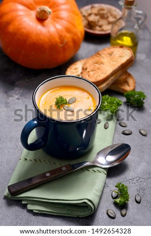 Pumpking soup in a mug, fresh autumn hot soup, homemade healthy soup, cozy food concept #1492654328