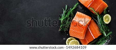 Salmon. Fresh raw salmon fish fillet with cooking ingredients, herbs and lemon on black background, top view, banner #1492684109
