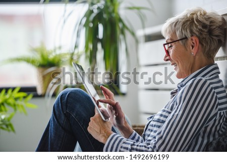 Senior woman using digital tablet at home. The use of technology by the elderly. Royalty-Free Stock Photo #1492696199