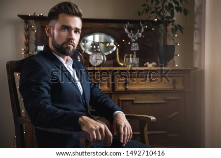 Portrait of handsome bearded man wearing black classic suit #1492710416