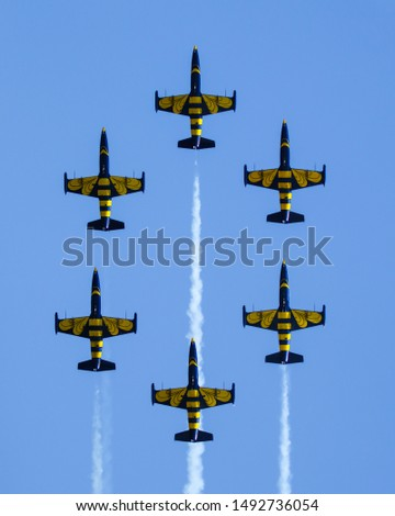 "The ""Baltic Bees"" aerobatic show team performing a formation of 6 jet-propelled planes. Clear sky, clean picture, suitable for screen saver or background. 8x10 portrait orientation."