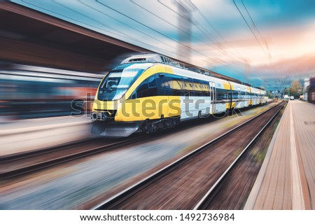 High speed yellow train in motion on the railway station at sunset. Modern intercity passenger train with motion blur effect on the railway platform. Industrial. Railroad and blurred background #1492736984