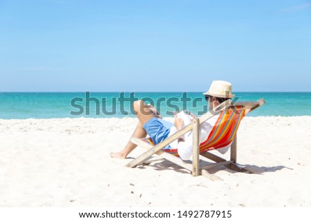 A handsome man relaxing on a book reading on the beach. Summer Vacation. Smelling asian man relaxing and reading book on the beach, so happy and luxury in holiday summer, outdoors blue sky background. #1492787915