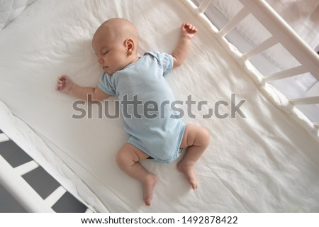 Top view wide angle sleeping newborn baby lies in a crib arms and legs outstretched, baby sleep Royalty-Free Stock Photo #1492878422