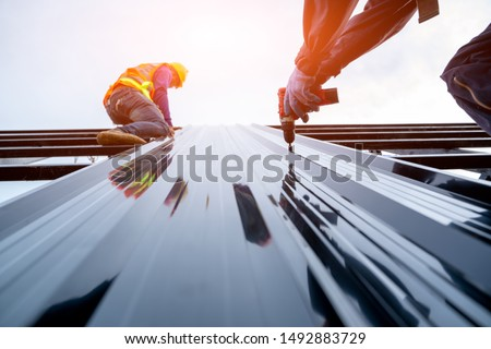 Roofer worker in protective uniform wear and gloves, using air or pneumatic nail gun and installing asphalt shingle on top of the new roof,Concept of residential building under construction. #1492883729