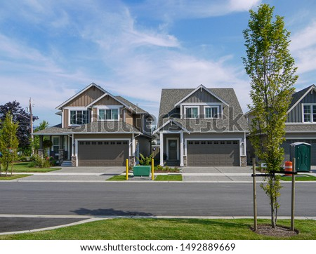 Brand new residential houses with concrete driveway and asphalt road in front #1492889669