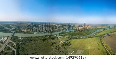Aerial view (drone view) on a sunny summer day over the Don River at the intersection with the M4-Don motorway. Road junction, bridge and port. The high right bank and the city of Aksai on its hills #1492906157